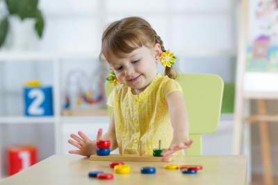 female kid playing table toys indoor